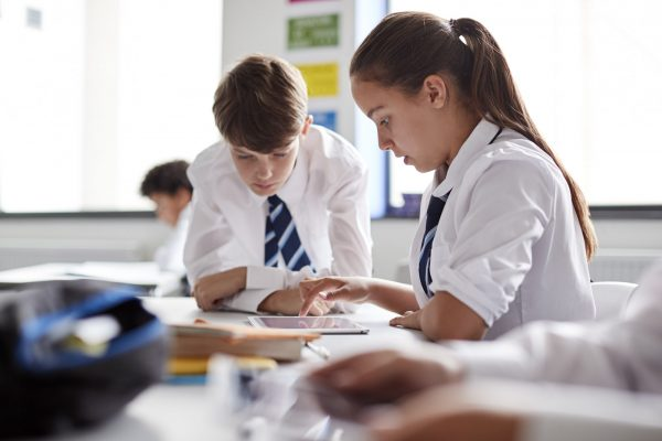 Two High School Students Wearing Uniform Working Together At Desk Using Digital Tablet